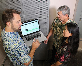 Tad Glauthier (Stem, Inc. vice president of Hawaii operations) shows Stem's electricity use dashboard to Leon Dodson (CFO of Watanabe Floral) and Dora Nakafuji, director of Hawaiian Electric's Renewable Energy Planning Division)