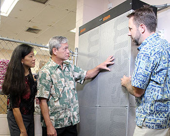 Dora Nakafuji, director of Hawaiian Electric's Renewable Energy Planning Division) and Leon Dodson (CFO of Watanabe Floral) look over the new energy storage system with Tad Glauthier (Stem, Inc. vice president of Hawaii operations)